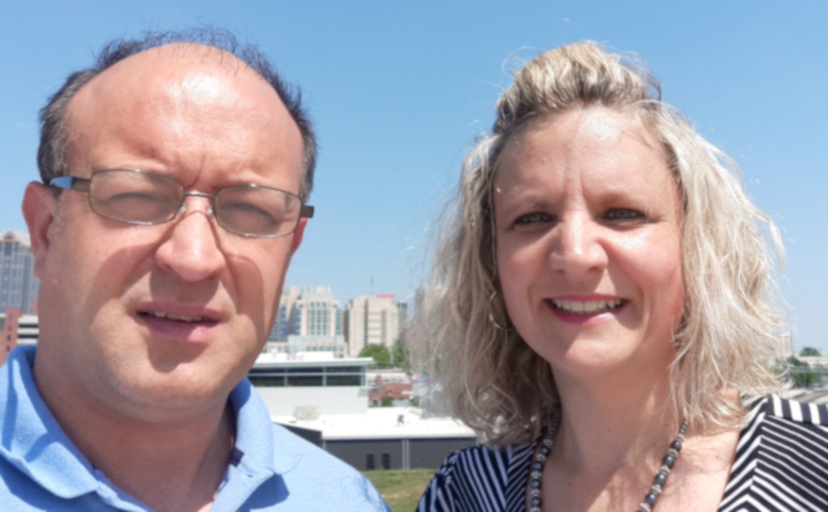 Bill Helmken, the company owner, and his wife Meigan Helmken pictured with downtown Raleigh, NC in the background